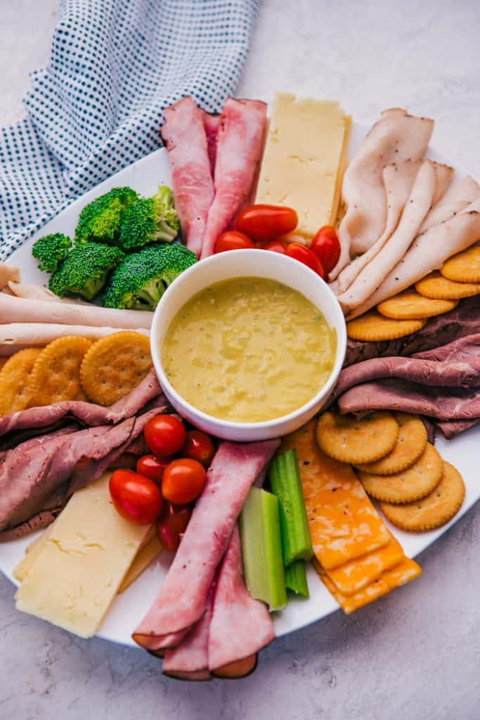 carolina mustard dip in a white bowl in center of a plate filled with meats, cheeses, crackers, and veggies