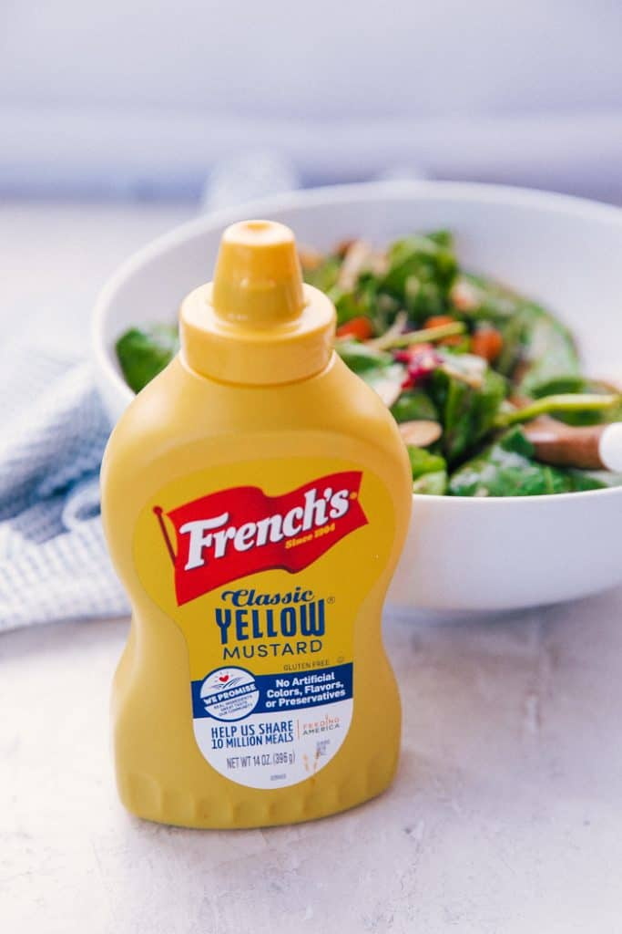 yellow mustard bottle in front of a bowl of copycat dorothy lynch salad