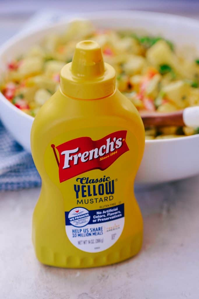 yellow mustard bottle in front of a bowl of tangy southwest dressing potato salad