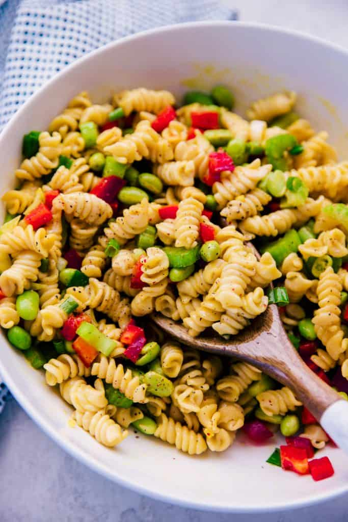 mustard ginger pasta salad in a white serving bowl with wooden serving spoon