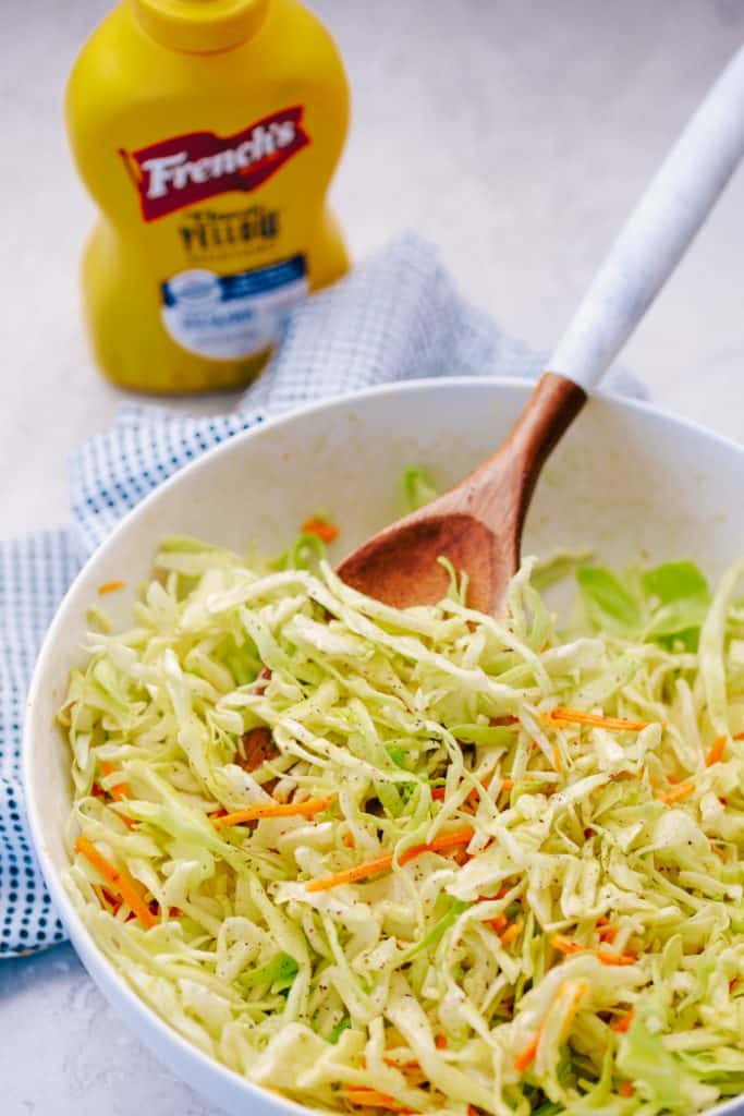 tangy coleslaw in a white bowl next to mustard bottle