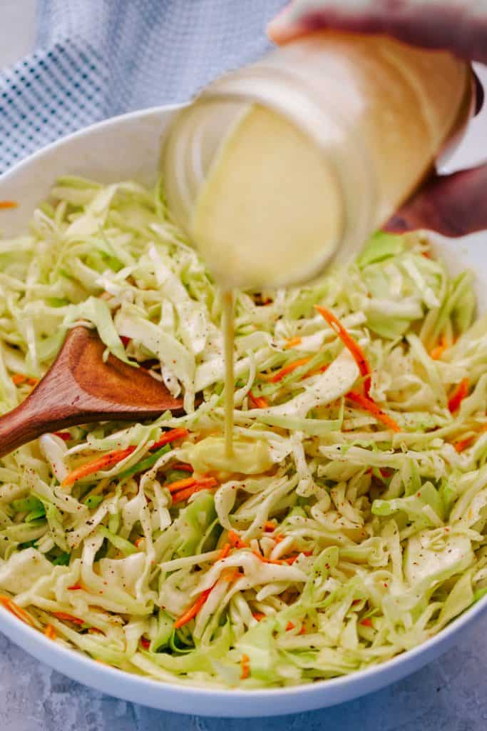 tangy dressing being poured from mason jar on sliced cabbage coleslaw in a white bowl