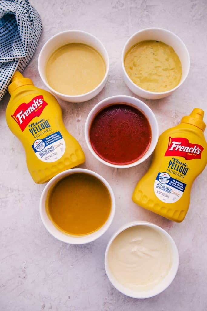 5 easy dressings in white bowls next to 2 bottles of french's yellow mustard