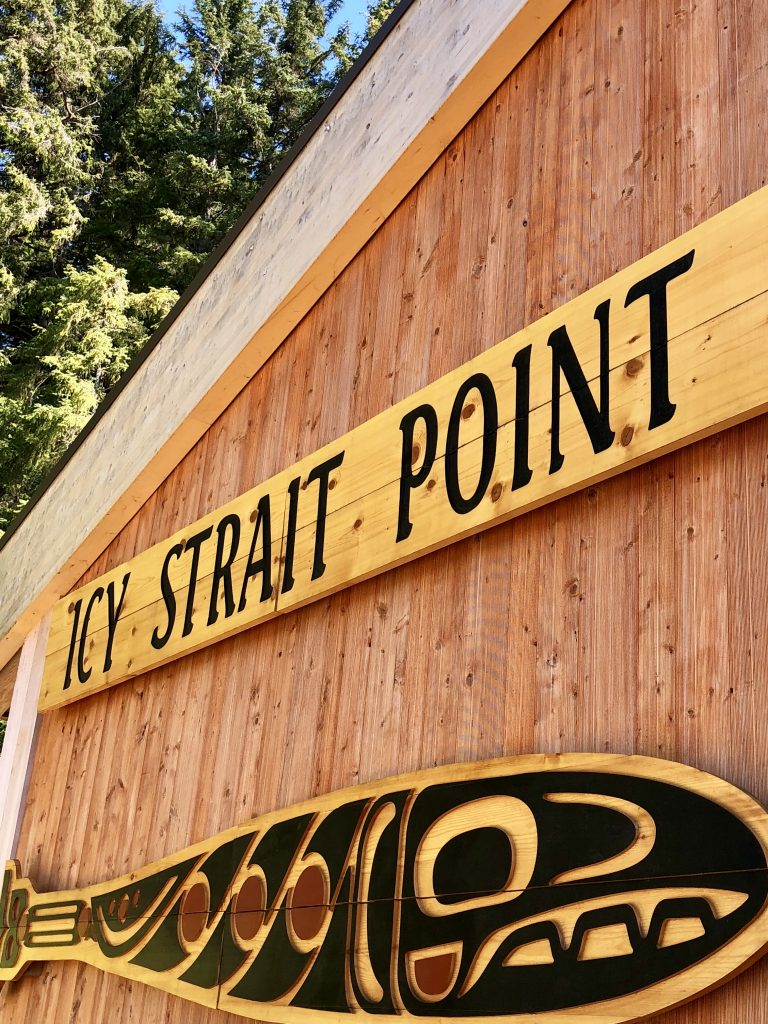 "wooden building with a wooden fish carving and a sign that reads ""icy strait point"""