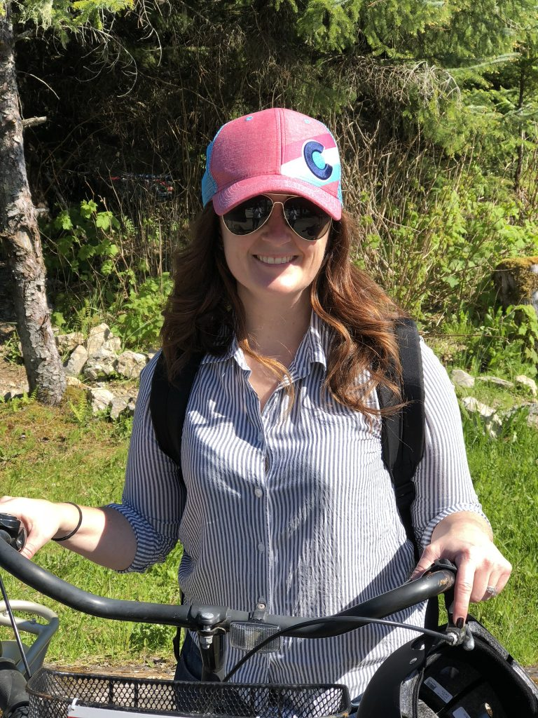 sandra standing on trail with a bike