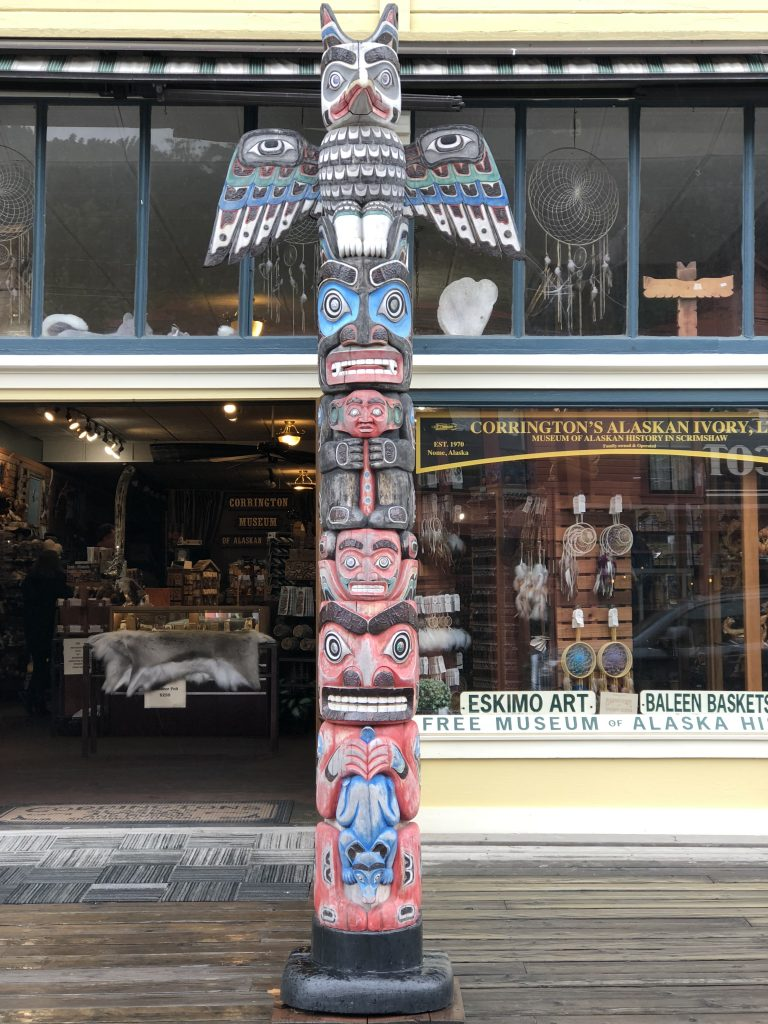 front of a shop with a carved eskimo pole