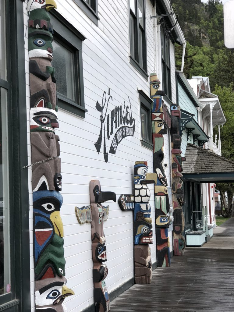 outside of a shop with wooden animal carvings on side of building