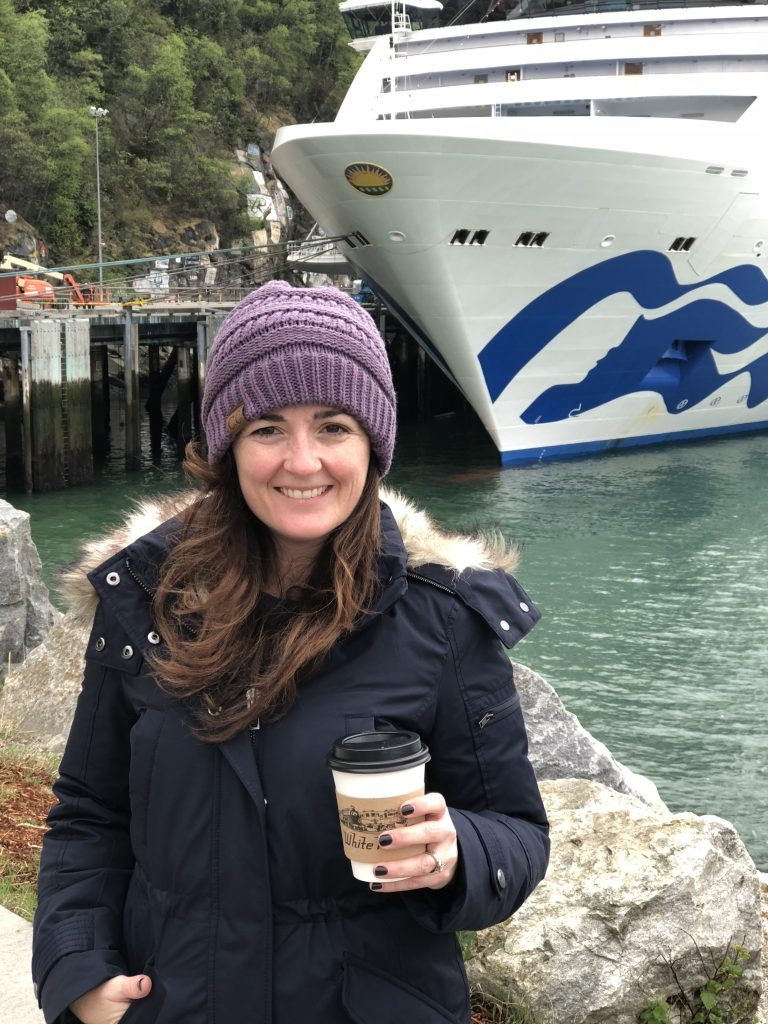 sandra in front of cruise ship holding a cup of coffee