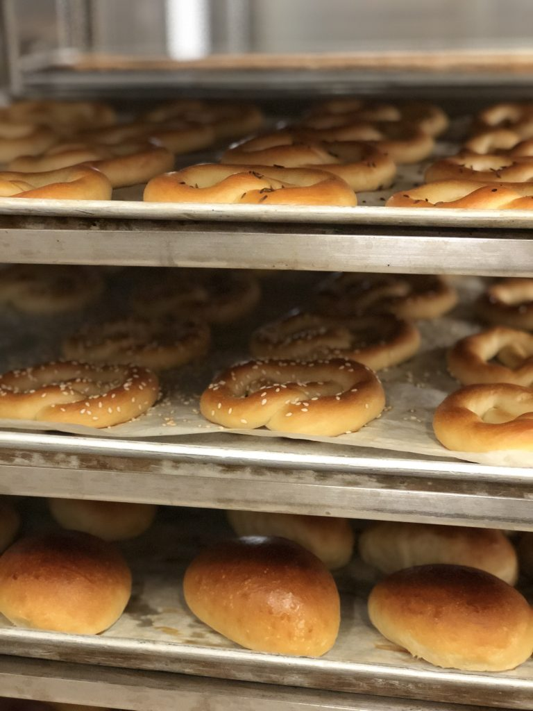 photo of fresh pretzels and rolls on sheet pans in bakery