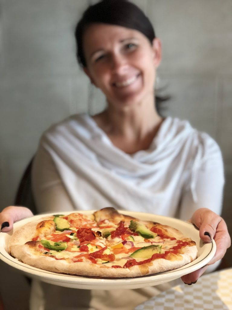 photo of a woman holding out a plate with a personal sized pizza