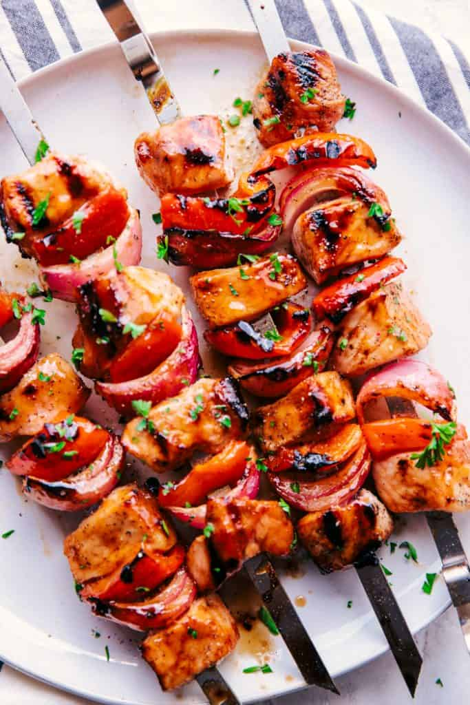 grilled pork skewers on a white plate