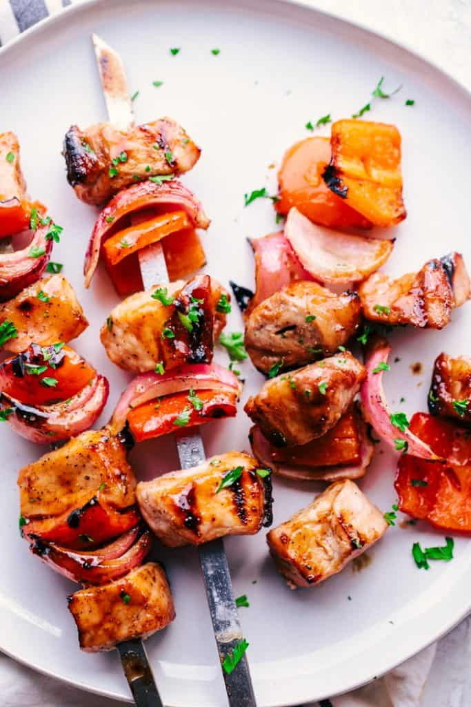 3 grilled pork skewers on a plate with one skewer removed