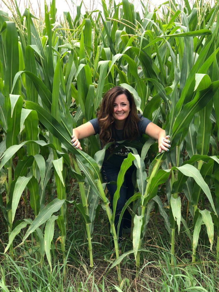 sandra in a corn field between corn stalks