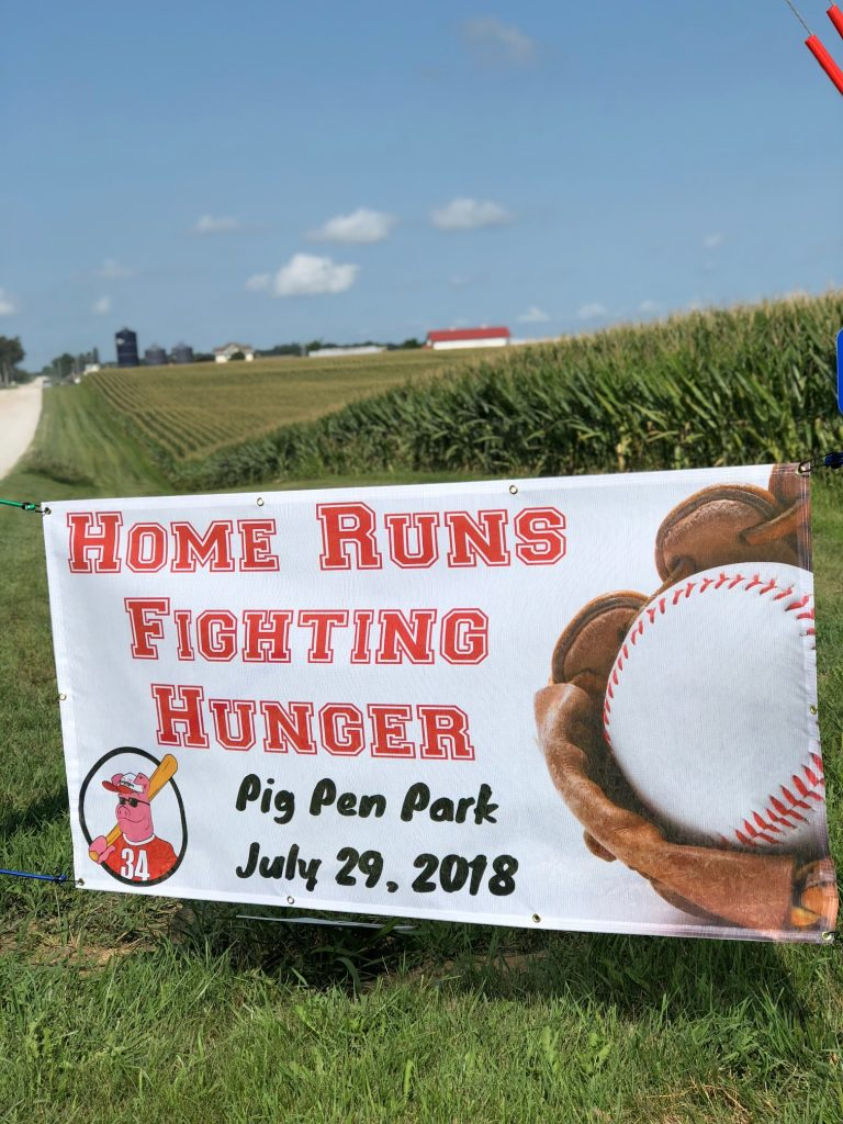 "sign that reads ""home runs fighting hunger. pig pen park, july 29, 2018"""