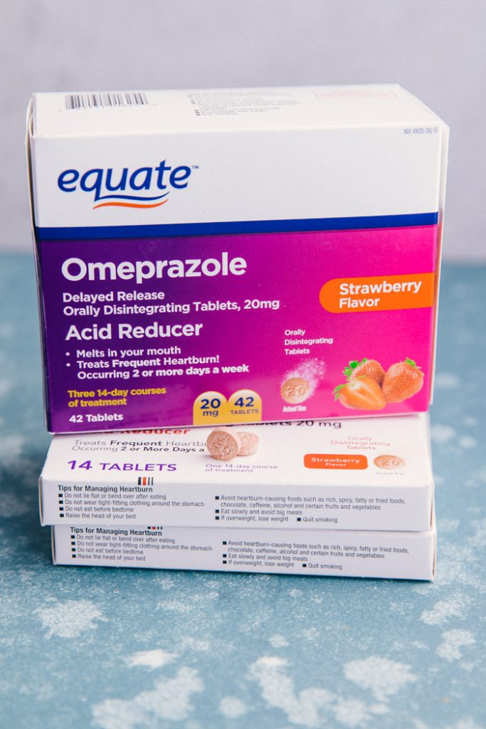box of omeprazole strawberry flavor standing on 2 smaller boxes