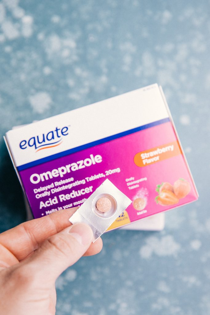box of omeprazole acid reducer tablets with 1 foil pack with a pill close up