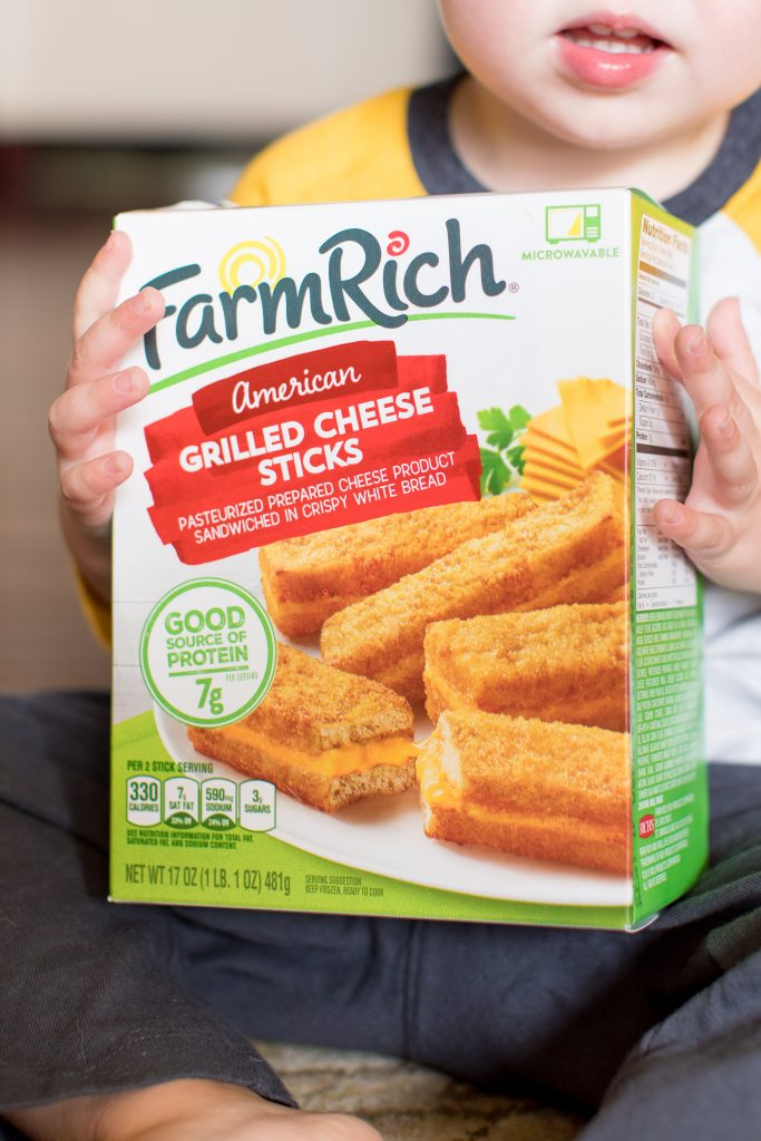 photo of a toddler holding a box of farm rich grilled cheese sticks
