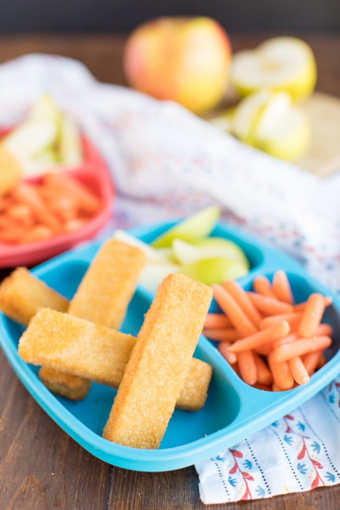 grilled cheese sticks on a blue kid's plate with baby carrots and apple slices