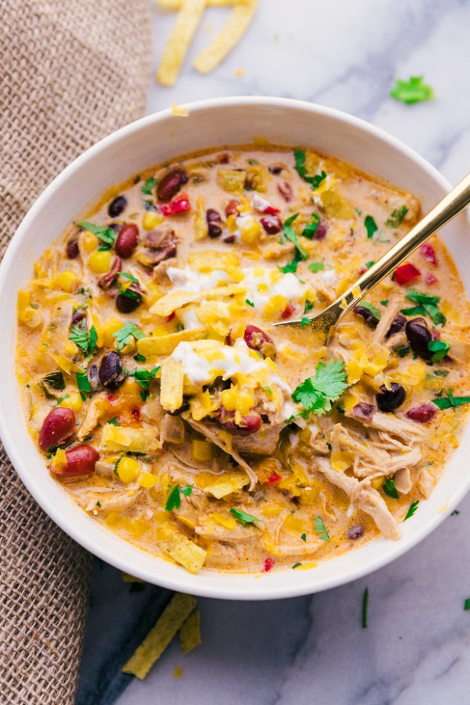 photo of a bowl of chicken tortilla soup with a spoon and garnishes