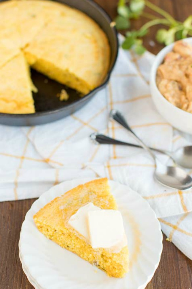 photo of a slice of cornbread on a plate with butter on top, and skillet with cornbread sliced in it
