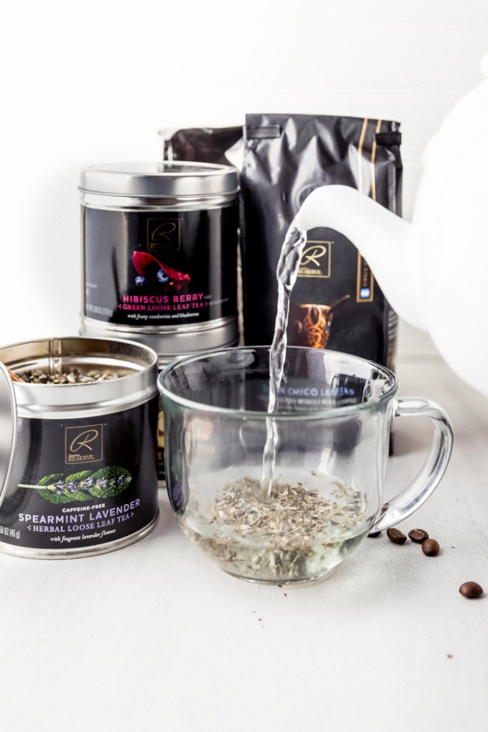 photo showing hot water from a kettle being poured into a glass mug with loose leaf spearmint lavender tea, with a bag of coffee beans and 3 jars of loose tea