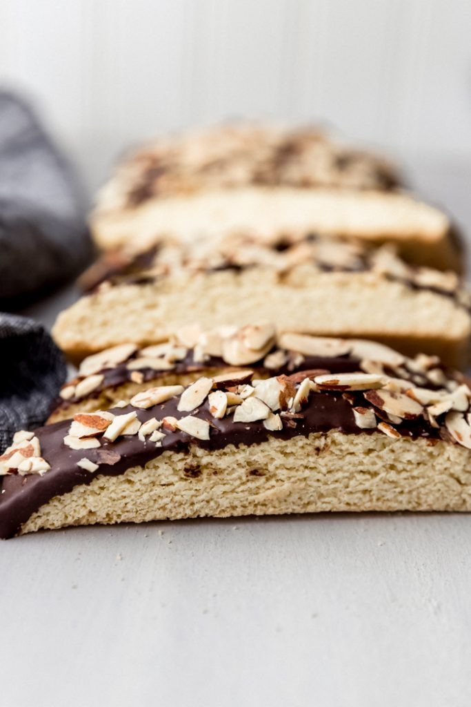 close up of biscotti dipped in chocolate and almonds on a counter, laid in a row