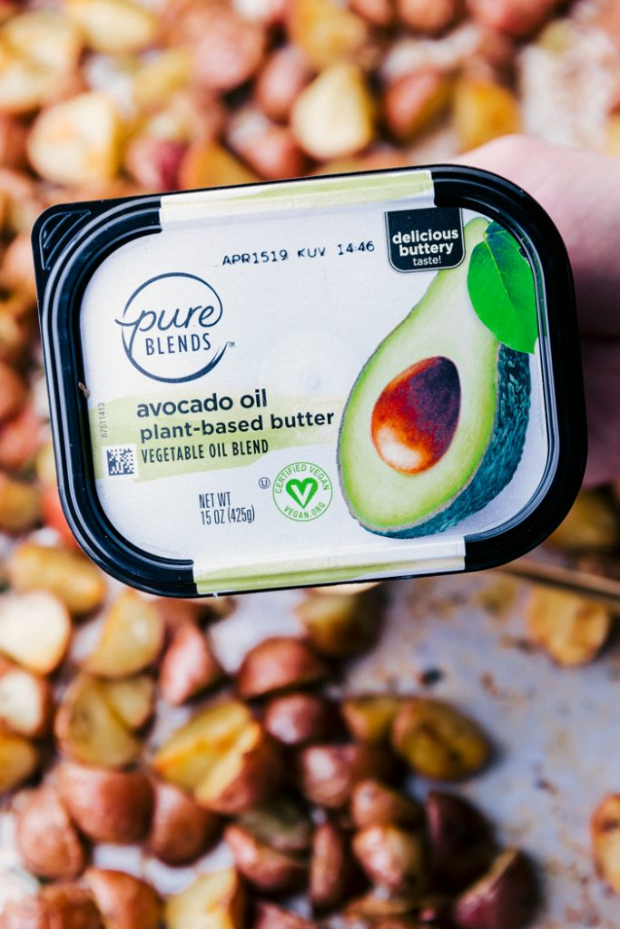 up close tub of pure blends avocado oil plant-based butter, with roasted potatoes on a sheet pan in background
