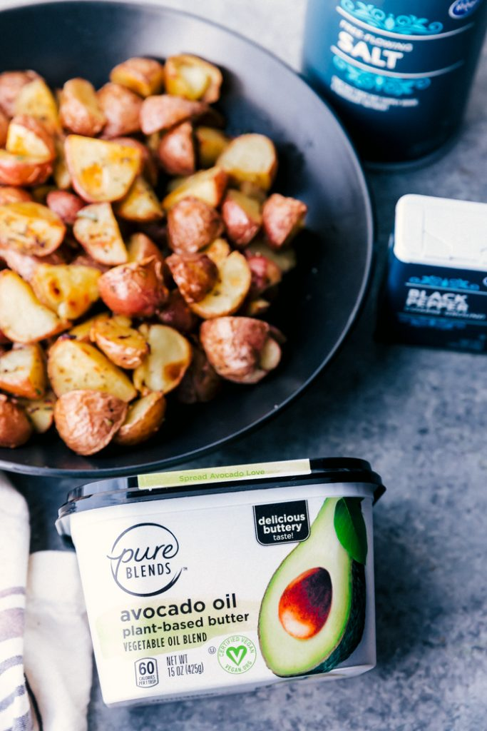 roasted potatoes in a black bowl with avocado oil butter tub on counter, with salt and pepper containers