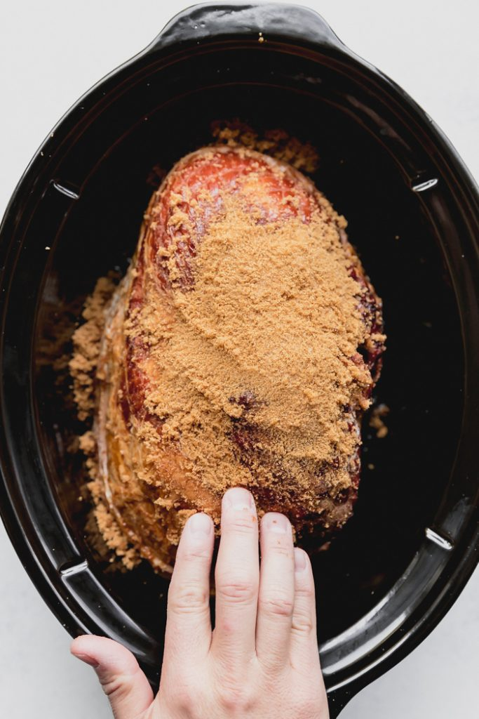 photo showing the ham in a crockpot, covered in brown sugar