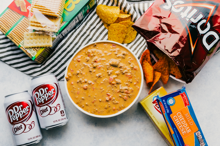 overhead photo of easy beef queso, with crackers, doritos, blocks of cheese, and dr. pepper on sides