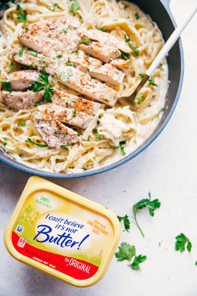 photo of Skinny Alfredo Sauce on pasta with chicken in a skillet, next to a tub of I can't believe it's not butter!