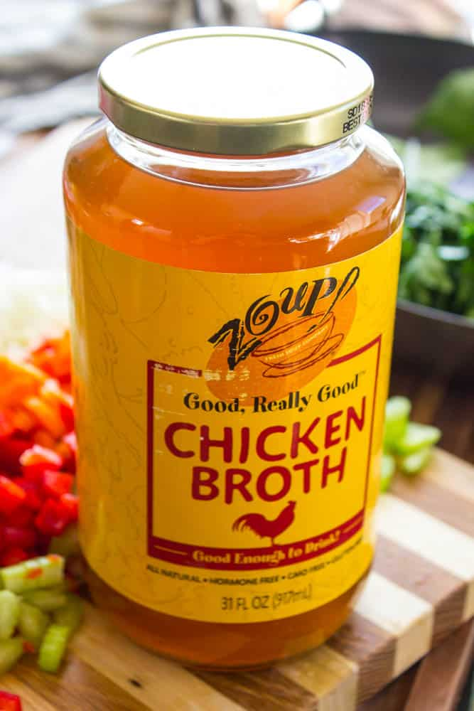 photo of a jar of zoup chicken broth with cut up veggies on a cutting board in background