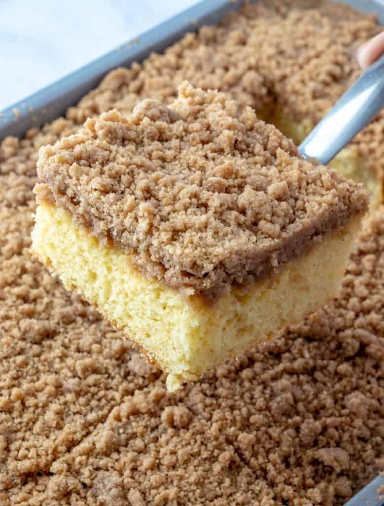photo showing a slice of Cinnamon Streusel Coffee Cake pulled out of pan on a metal spatula
