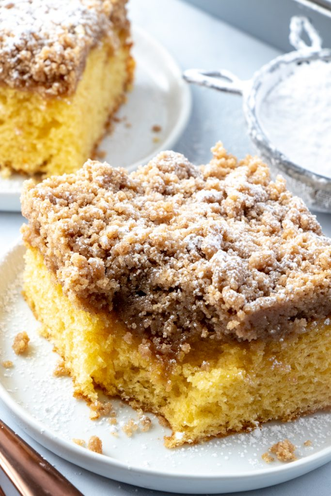 photo of Cinnamon Streusel Coffee Cake slice on a white plate with bite taken out