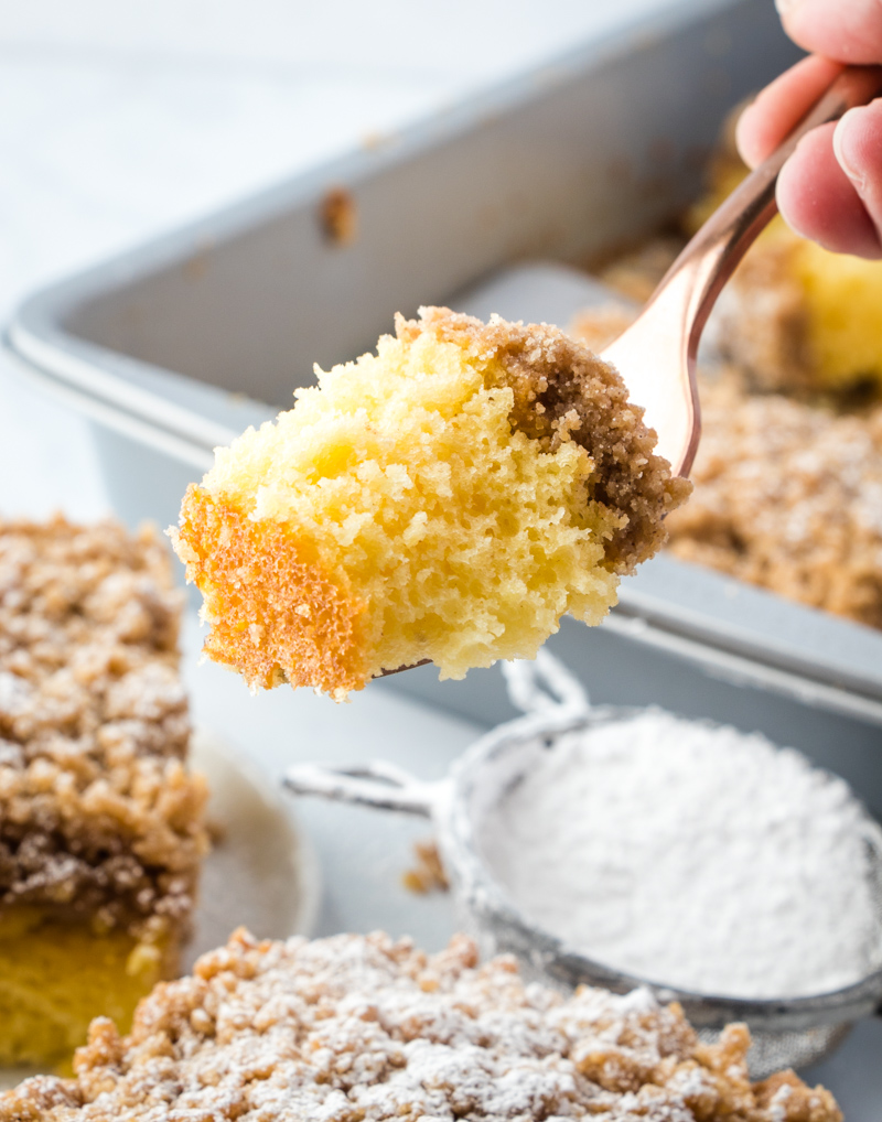 photo showing a bite of Cinnamon Streusel Coffee Cake on a fork, with pan of cake in background