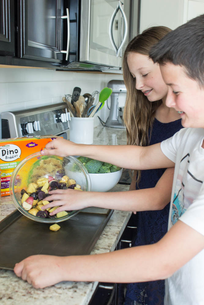 photo of 2 kids pouring halved and seasoned mini potatoes from a glass bowl onto sheet pan