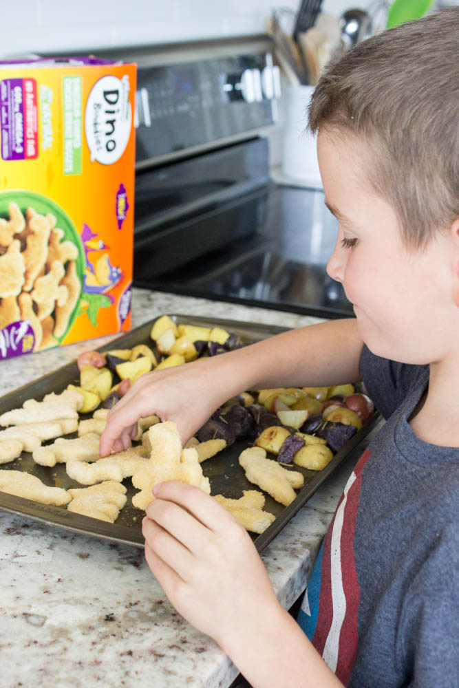 photo of boy arranging dino nuggets on a metal sheet pan