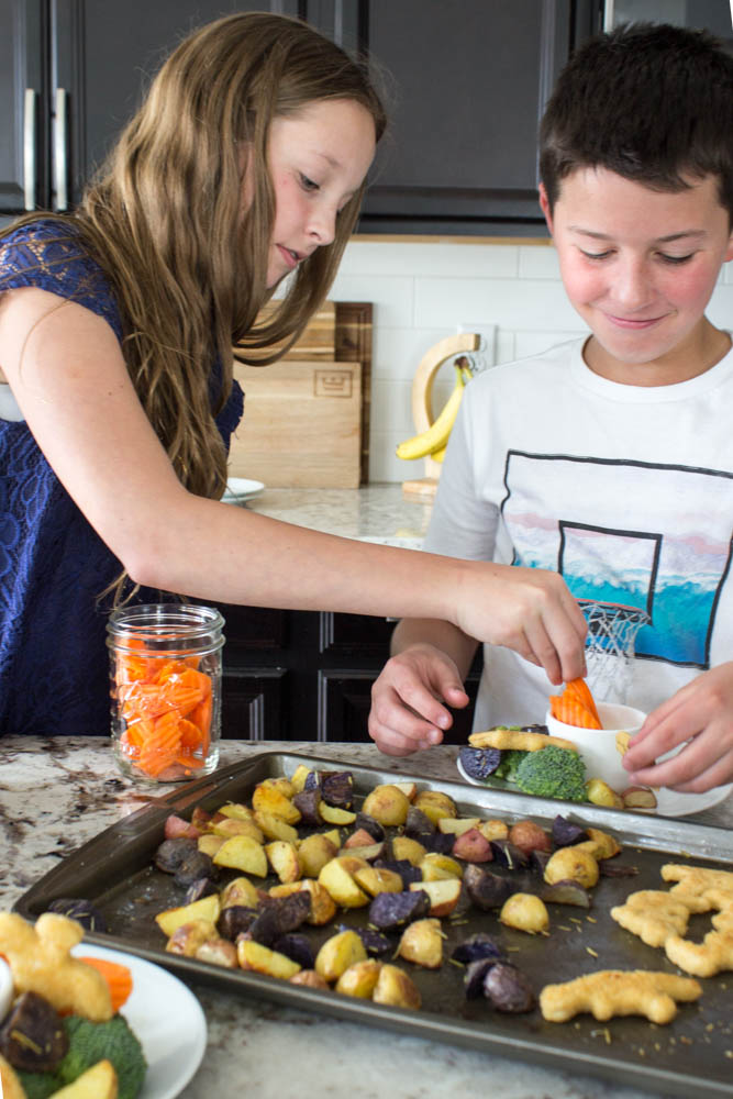 photo of 2 kids building a plate of food from the sheet pan dinner