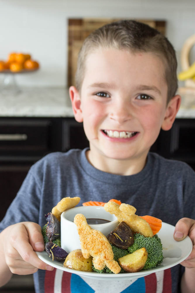 photo of a boy holding a plate of the sheet pan dinner