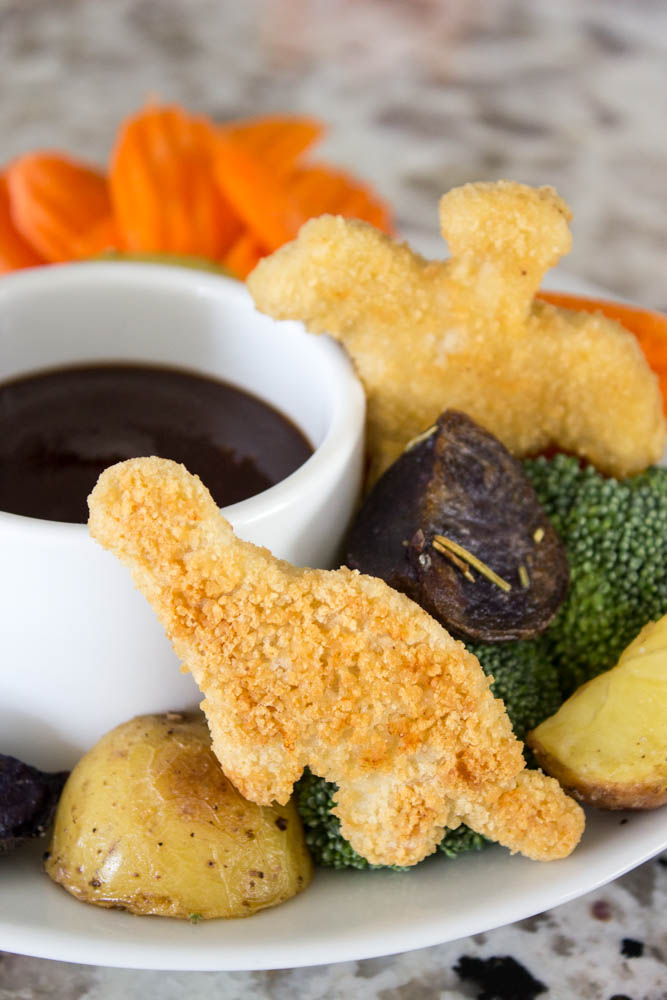 photo with cut potatoes, dino nuggets, cut carrots and broccoli with a small dipping bowl of barbecue sauce on a plate