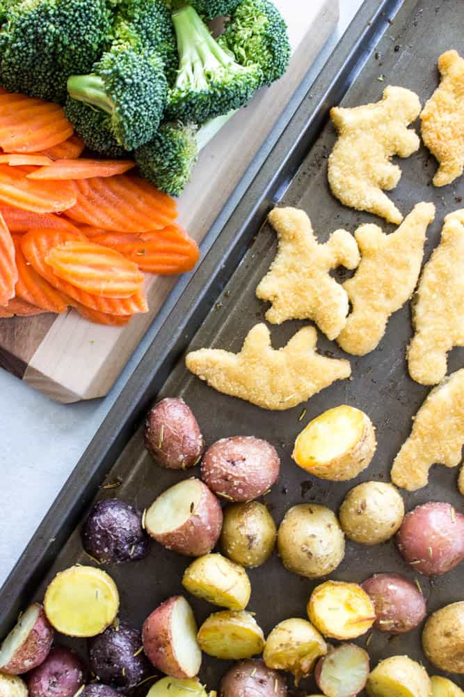 overhead photo of cut mini potatoes and dino nuggets on a sheet pan next to a cutting board with wavy cut carrots and broccoli florets