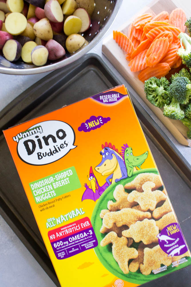 photo of a box of dino buddies nuggets on a tray with bowl of potatoes and cutting board with veggies