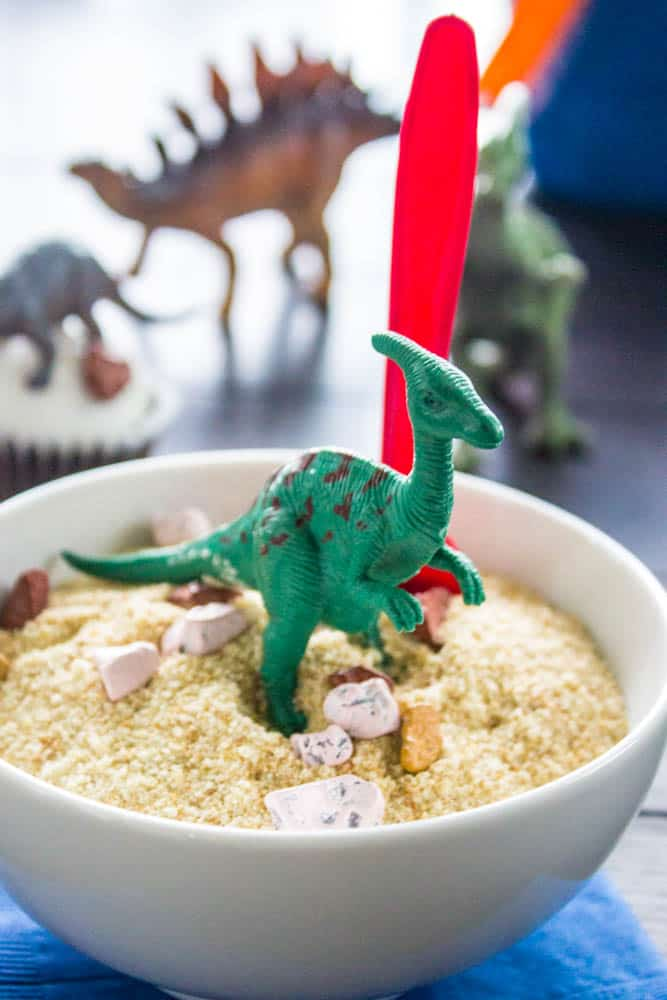 "photo of a bowl of breadcrumb ""sand"" with plastic toy dinosaur on top"