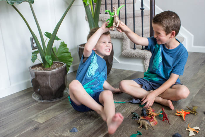 photo of 2 boys playing with plastic dinosaur toys