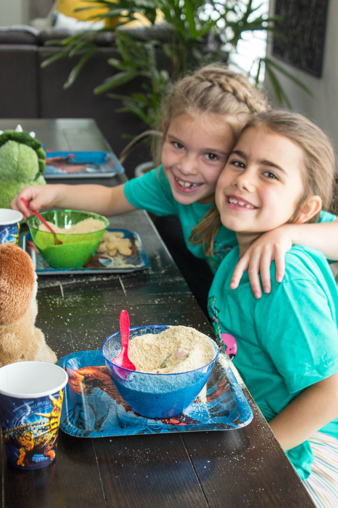 photo of two young girls with arms around each other, sitting at a table with dino dig bowls in front of them