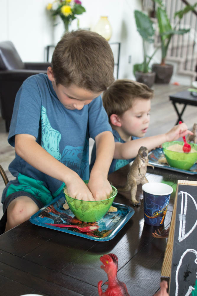 photo of 2 young boys digging for dino nuggets in green bowls