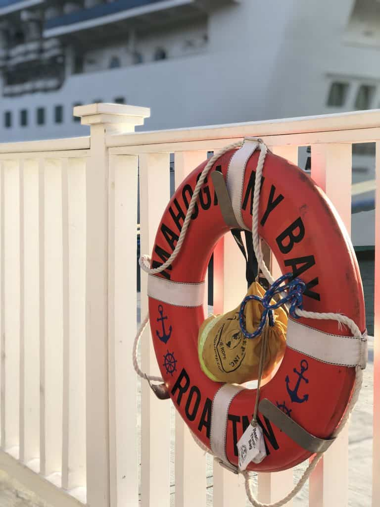 "photo of a lifebuoy that says ""mahogany bay"" hanging on a white fence by cruise ship"