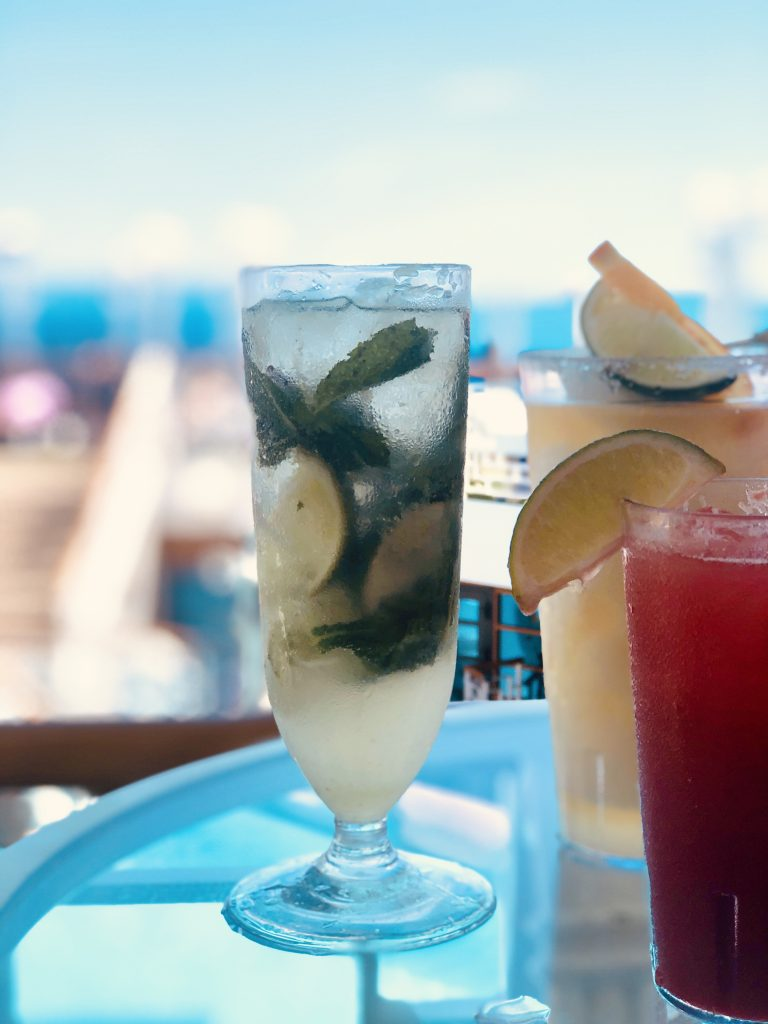 Photo of virgin mojito and other drinks with lime slices on a glass table on cruise deck