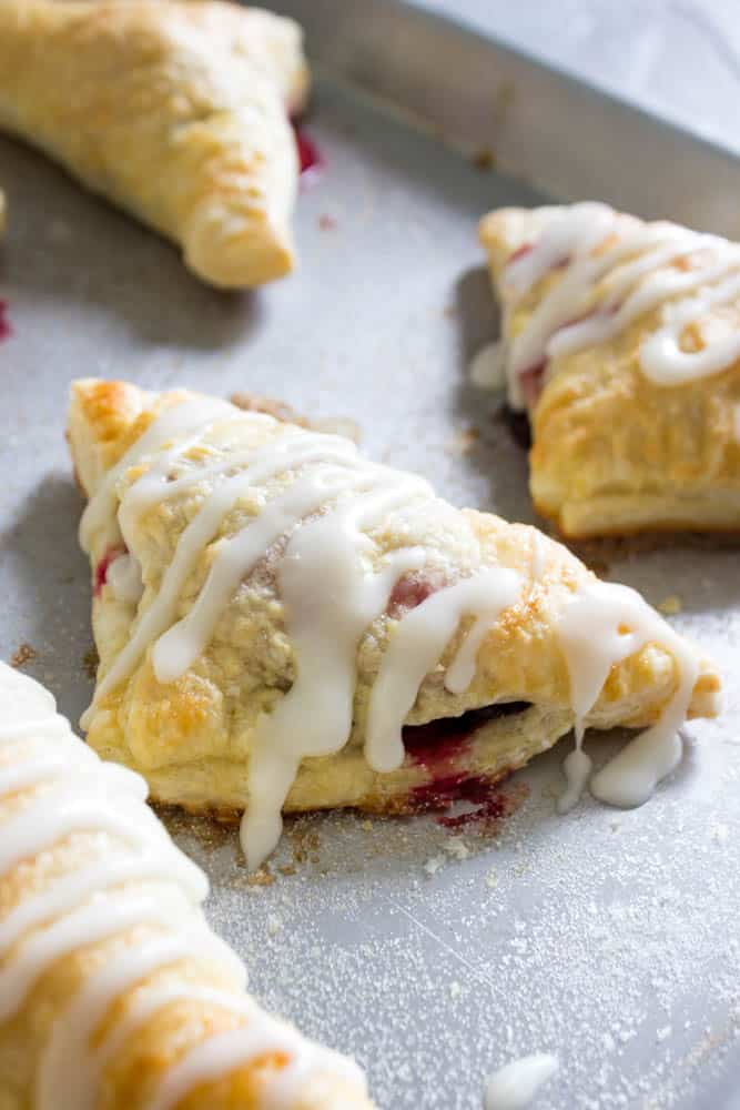 photo of Chocolate Raspberry Turnovers  on sheet pan with drizzed white icing