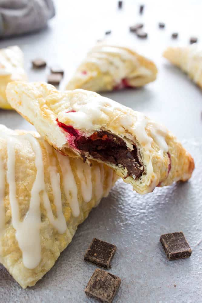 photo of Chocolate Raspberry Turnovers in stack, 1 with bite taken out showing chocolate and raspberry inside